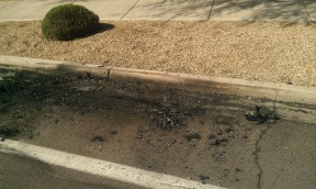 Ashes and road damage from the car fire.